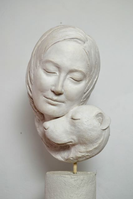 PORTRAIT OF A DOG RESTING ITS HEAD ON A WOMAN SCULPTURE