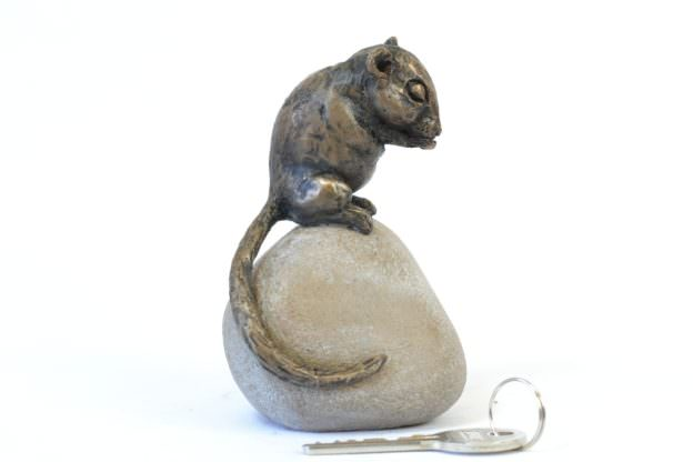 DORMOUSE SITTING ON STONE SCULPTURE