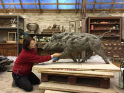 Tanya Russell sculpting a wild boar in her studio using clay
