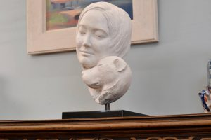 Portrait of a Dog Resting its Head on a Woman Statue