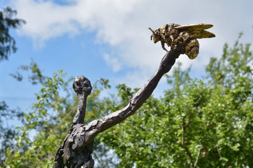bronze woman and bee sculpture